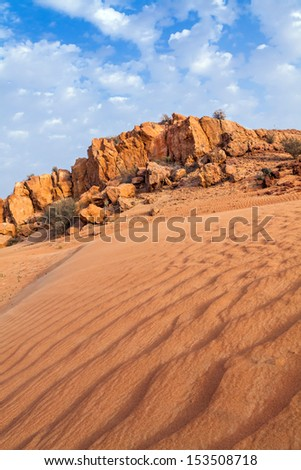 Red desert in Dubai, Rocks against a blue sky and white clouds