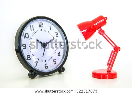 Red desk lamp focusing on alarm clock on white background