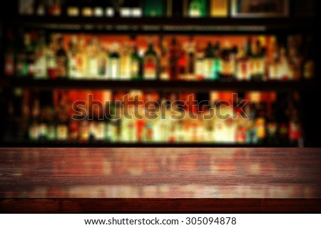 red desk top in blurred bar background  - stock photo