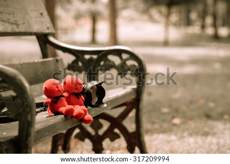 Red devil doll couple sitting on chair in the park. Soft focus, Vintage color. - stock photo
