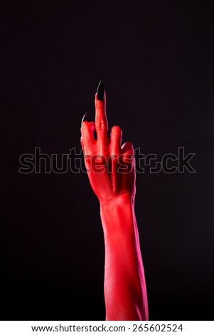 Red devil hand with black nails showing middle finger, studio shot on black background  - stock photo