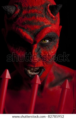 Red devil woman with her trident. Low key lighting. - stock photo