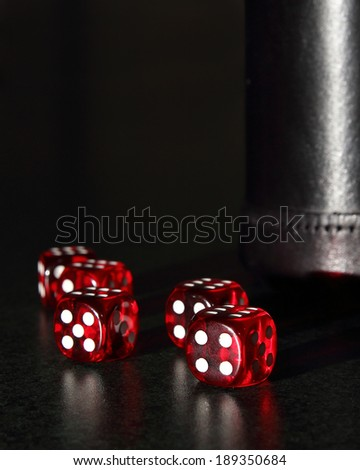 Red dice and a black leather dice cup shot with mood lighting.