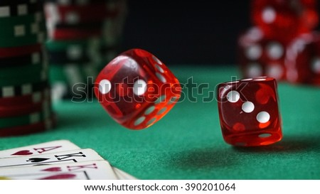 Red dice, casino chips, cards on green felt - stock photo