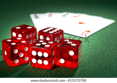 Red dice, four aces  on a green felt  - stock photo