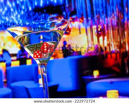 red dice in the cocktail glass in front of lounge bar casino, casino concept - stock photo