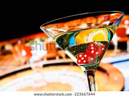 red dice in the cocktail glass in front of roulette wheel, casino series - stock photo