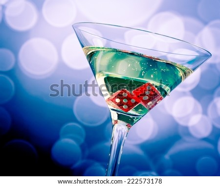 red dice in the cocktail glass on blue bokeh background - stock photo