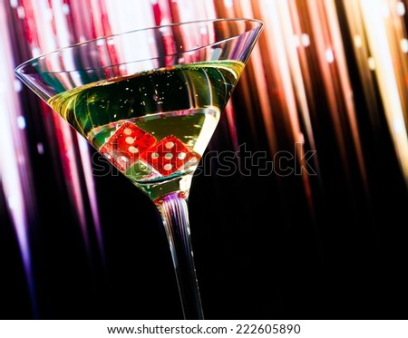 red dice in the cocktail glass on colorful gradient background with space for text - stock photo