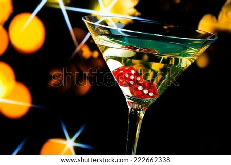red dice in the cocktail glass on gold bokeh and stars background - stock photo