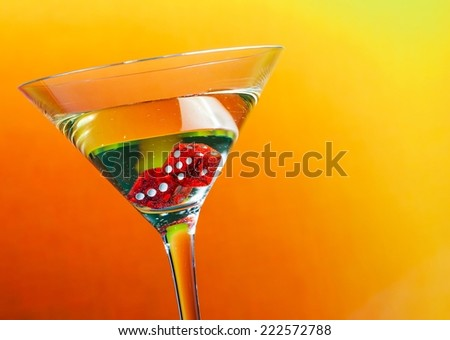red dice in the cocktail glass on golden gradient background - stock photo