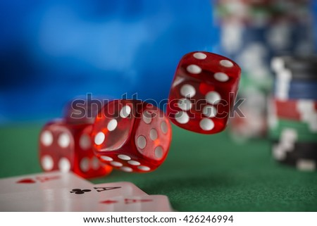 Red dice rotates and will fall 7, casino chips, cards on green felt - stock photo