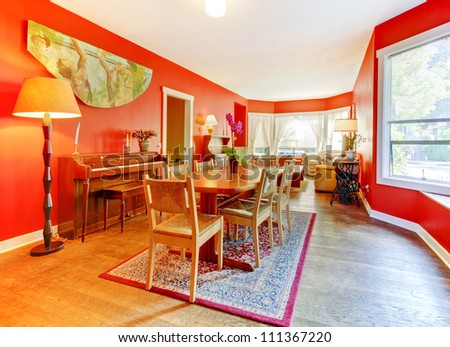 Red dining room with piano, hardwood floor and many windows. - stock photo