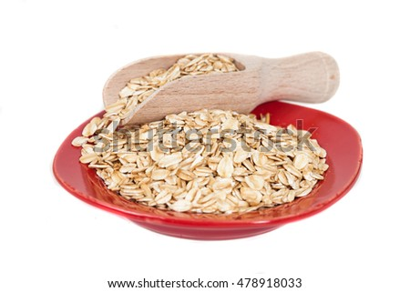 red dish  with oats flakes pile on white background.