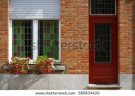 Red door, flowers and window of old house in european city. Bruges (Brugge), Belgium, Europe. Classic colorful apartment with a decoration near the entrance. Beautiful architecture.  - stock photo