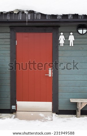 Red door to public toilet in a green wood building - stock photo