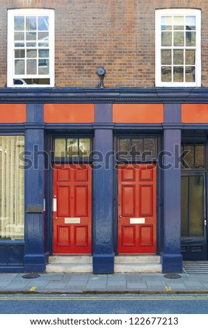 Red doors on building Exterior of modern building with two red doors, street in foreground.
