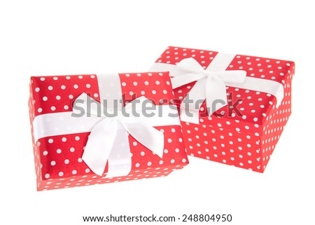 Red dotted presents with ribbon and satin bow isolated over white background