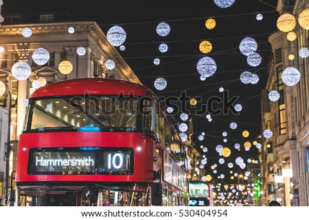 Red double decker bus in London during Christmas time. Lights and decorations over the famous London street reflecting on the bus surface. Travel and tourism concepts