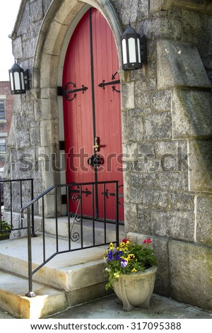 Red, double doors of arched entrance to St. James Episcopal Church, with flowers in pot, from side view, downtown Keene, New Hampshire. - stock photo