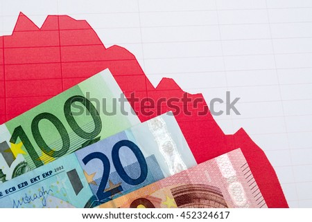 Red down trend graph  and banknotes on trading workplace