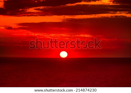 Red dramatic sunset over calm sea - stock photo