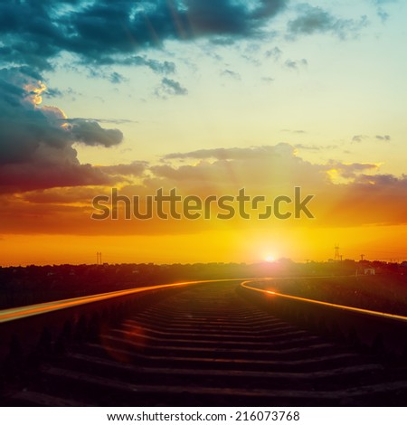 red dramatic sunset over railroad with reflections - stock photo