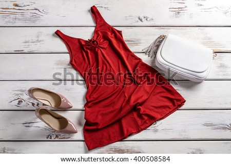 Red dress and heel shoes. Bright evening outfit on shelf. Evening clothes set for women. Plain yet attractive clothing. - stock photo