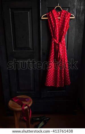 Red dress in a white dots  on a wooden hanger ,black shoes on the floor and red tie on the stool. Fashion, relations concept