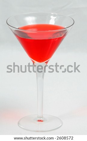 red drink in martini glass against white background