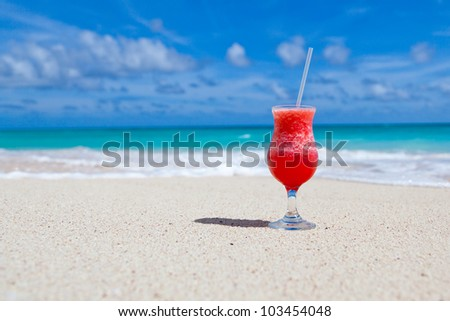 red drink with a straw on the white beach with ocean and sky in the background - stock photo