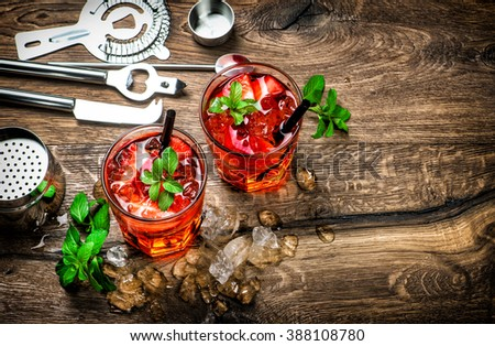 Red drink with ice, mint leaves and strawberry. Cocktail, campari, aperol, caipirinha, mojito, soda water. Dark toned picture - stock photo