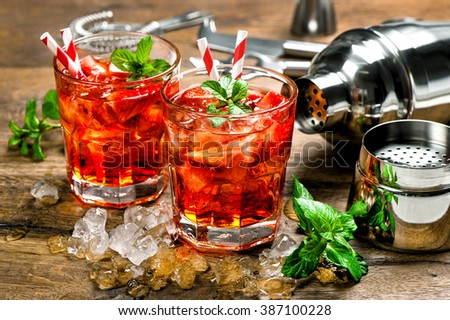 Red drink with strawberry, mint leaves, ice. Cocktail making bar accessories - stock photo