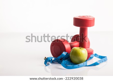 Red dumbbells weight with measuring tape and green apple for diet concept on white background - stock photo