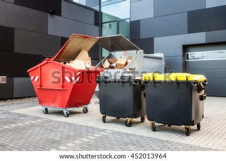 Red dumpster, recycle, waste and garbage bins near new office building. Backyard view - stock photo