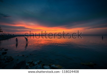 Red dusk at the ocean with people - stock photo