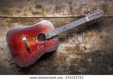 Red Dusty Guitar On A Wooden Table