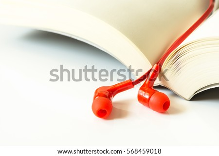 Red earphone with book under the white background.
