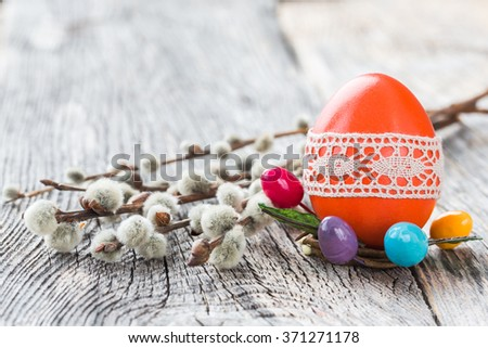 Red Easter egg decorated with lace and willow branch on wooden background. Selective focus, copy space  - stock photo