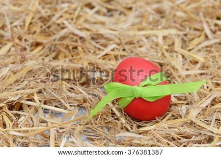 red easter egg lying on straw