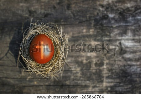 Red easter egg with cross in a nest on blurred grunge wooden background : Jesus born baby nativity resurrection symbol : Easter Sunday Holy week: All saints' day spiritual concept: Christian spirit   - stock photo