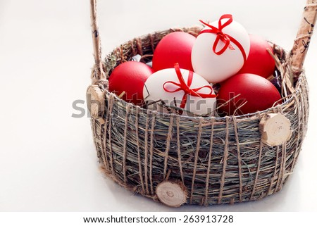 Red Easter Eggs and White Easter Eggs Decorated with Red Ribbon Bow in a Rustic Basket - stock photo