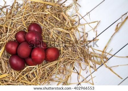 Red Easter eggs in a straw nest. Happy Easter!