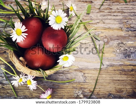 Red easter eggs in basket with flowers - stock photo