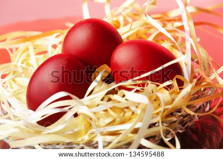 red easter eggs in  the nest against color background - stock photo