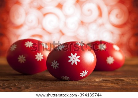 Red Easter eggs on wooden table and patterned background - stock photo