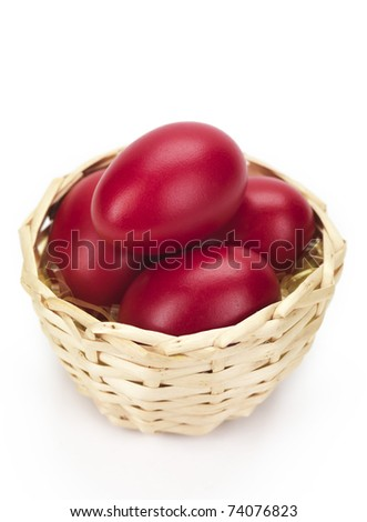 red eggs in a wicked basket isolated on a white background