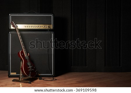 Red electric guitar and classic amplifier on a dark background
