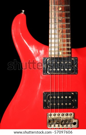 Red electric guitar isolated on black.