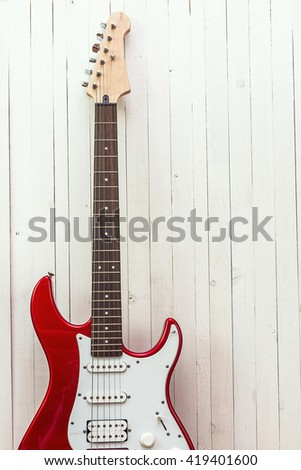 Red electric guitar on a background of white painted boards. Place for text.  - stock photo